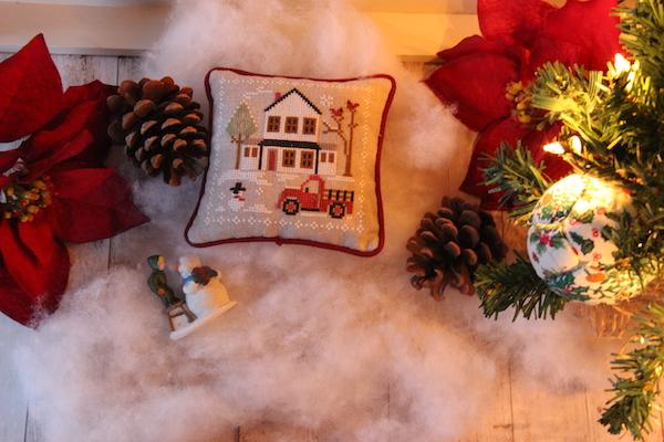 Kerstdecoratie met een geborduurde farmhouse scene