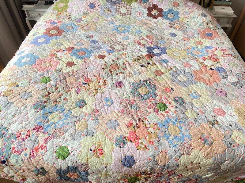 Grote bloemenquilt op bed